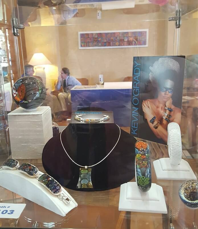One of the coziest spots to catch a cup of coffee in the morning is the lobby at the Riverpark Inn with its warn fireplace.  You can get a great overview of the show by perusing the display cases in the lobby - like this one from glass artist Kevin O'Grady.